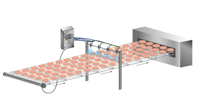 beef patties on a conveyor being sprayed